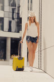 Attractive woman with suitcase walking after arrival. Travel, adventure, teenage journey concept. Walking woman wearing denim shorts, white top and sun hat Stock Photos