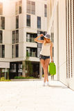 Attractive woman with suitcase walking after arrival. Travel, adventure, teenage journey concept. Walking woman wearing denim shorts, white top and sun hat Stock Image
