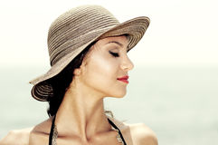 Attractive woman with a sun hat on a tropical beach, eyes closed Royalty Free Stock Images