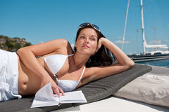 Attractive woman sunbathing on luxury boat Royalty Free Stock Photography