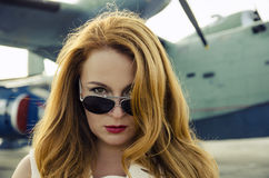 Attractive woman in sunglasses outside near military plane Royalty Free Stock Images