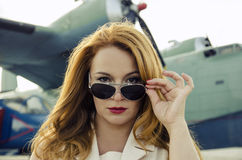 Attractive woman in sunglasses outside near military plane Royalty Free Stock Image