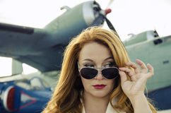 Attractive woman in sunglasses outside near military plane Stock Photo