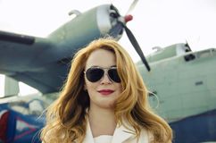 Attractive woman in sunglasses outside near military plane Royalty Free Stock Photos