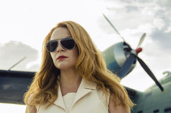 Attractive woman in sunglasses outside near military plane Royalty Free Stock Photo