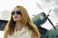 Attractive woman in sunglasses outside near military plane Stock Photos