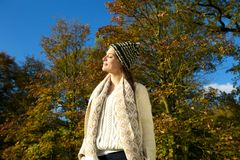 Attractive woman in sweater and hat enjoying the sun on an autumn calm day Stock Image