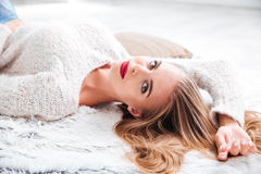 Attractive woman in sweater lying on the carpet at home royalty free stock image