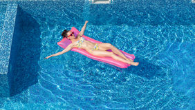 Attractive woman swimming on inflatable mattress in pool Royalty Free Stock Images
