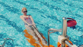 Attractive woman in a swimsuit doing exercises in the pool. Healthy lifestyle. Aqua aerobics in the open air stock video