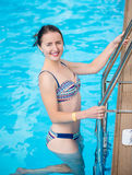 Attractive woman in swimsuit is going out of the pool, looking at camera and smiling Stock Photos