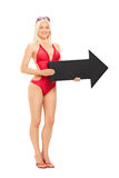 Attractive woman in swimsuit holding a big arrow Stock Photos