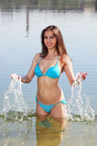 Attractive woman in the swimsuit play in a water Royalty Free Stock Photos