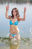 Attractive woman in the swimsuit play in a water Stock Photo