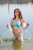 Attractive woman in the swimsuit play in a water Stock Image