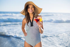 Attractive woman in swimsuit with straw hat holding cocktail Royalty Free Stock Photo