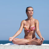 Attractive woman in swimwear doing yoga at the sea Royalty Free Stock Photography