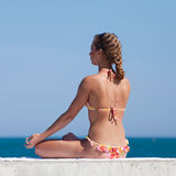 Attractive woman in swimwear doing yoga at the sea stock images