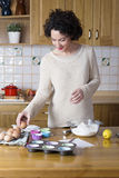 Attractive woman taking an egg to make a cupcakes recipe Stock Images