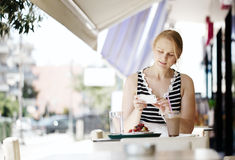 Attractive woman taking picture of a pastry on her Stock Image