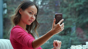 Attractive woman taking self portrait by mobile phone in cafe. Close up. Professional shot in 4K resolution. 086. You can use it e.g. in your commercial video Stock Image
