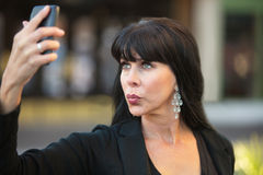 Attractive Woman Taking Selfie. With black cell phone Royalty Free Stock Photography
