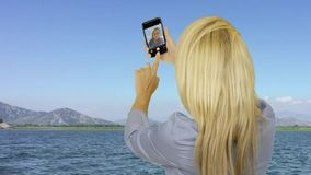 Attractive woman taking selfie photo on mobile during floating on sea yacht. Attractive woman taking selfie photo on mobile phone during floating on sea yacht stock video