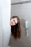 Attractive woman taking shower. Gorgeous woman behind curtain taking a shower at modern bathroom stock photography