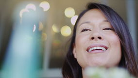 Attractive woman talking excitedly and cheerfully at a cafe table outdoors in slow motion stock video