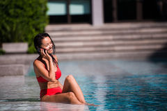 Attractive woman talking on her mobile phone by the poolside.  stock photos