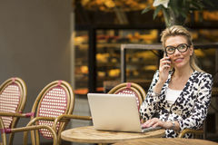 Attractive woman talking on mobile while sitting with a laptop in an outdoor summer cafe. Stock Photography