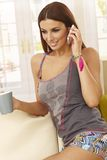 Attractive woman talking on mobilephone. Attractive young woman talking on mobilephone at home, smiling Stock Images
