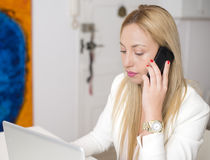 Attractive woman talking on the phone in front of computer. royalty free stock photos