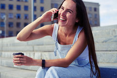 Attractive woman talking on the phone and laughing while sittin Royalty Free Stock Photography