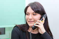 Attractive woman talking on phone in office Stock Photos