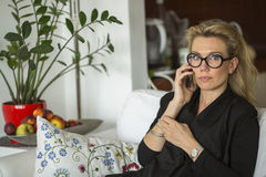 Attractive  woman talking on phone sitting on a sofa. Royalty Free Stock Images