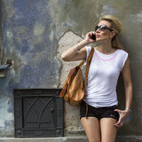 Attractive woman talking on the phone standing on the street of the old town. Stock Photo