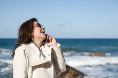 Attractive woman talking by phone to the sea Royalty Free Stock Photos