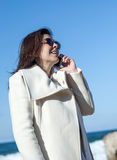 Attractive woman talking by phone to the sea Royalty Free Stock Images