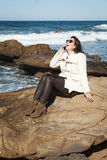 Attractive woman talking by phone to the sea Stock Photography