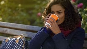 Attractive woman talking on smartphone, drinking hot coffee outdoors, chilly day. Stock footage stock photos