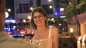 Attractive woman talking toast while romantic dinner and drinking wine in restaurant. Young woman drinking wine from. Glass together man at romantic date in stock video