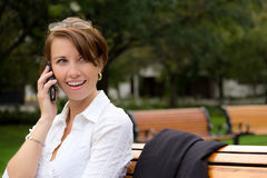 Attractive woman talks on mobile phone in the park Stock Photography
