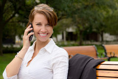 Attractive woman talks on mobile phone in the park Stock Images