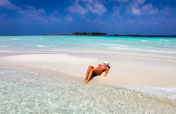 Attractive woman is tanning on a sandbank Royalty Free Stock Photography