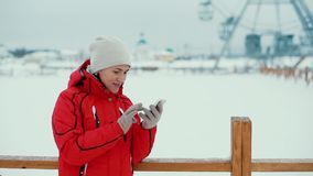 Attractive woman texting with her phone in winter scenery, outdoors stock footage