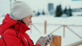 Attractive woman texting with her phone in winter scenery, outdoors stock video