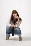 Attractive woman thinking. A studio view of an attractive young woman casually dressed in blue jeans, light shirt and loose necktie as she sits in a squatting Stock Photo