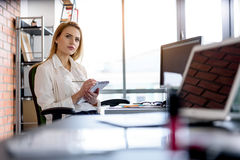 Attractive woman thinking seriously at her workplace against window Royalty Free Stock Photos