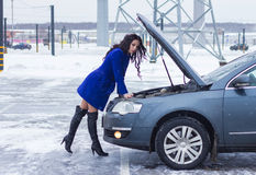 Attractive woman threw her leg back and looking under the hood of her car Stock Photo